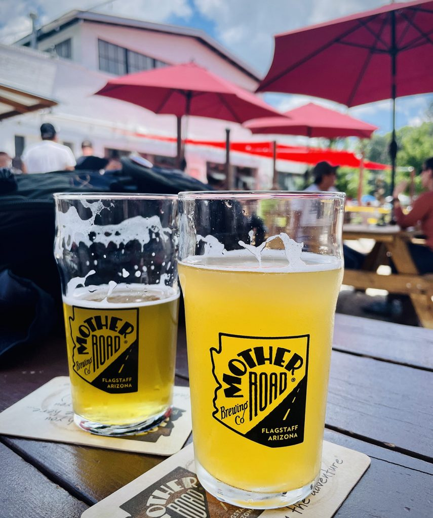 two pint glasses of beer on an outside patio table