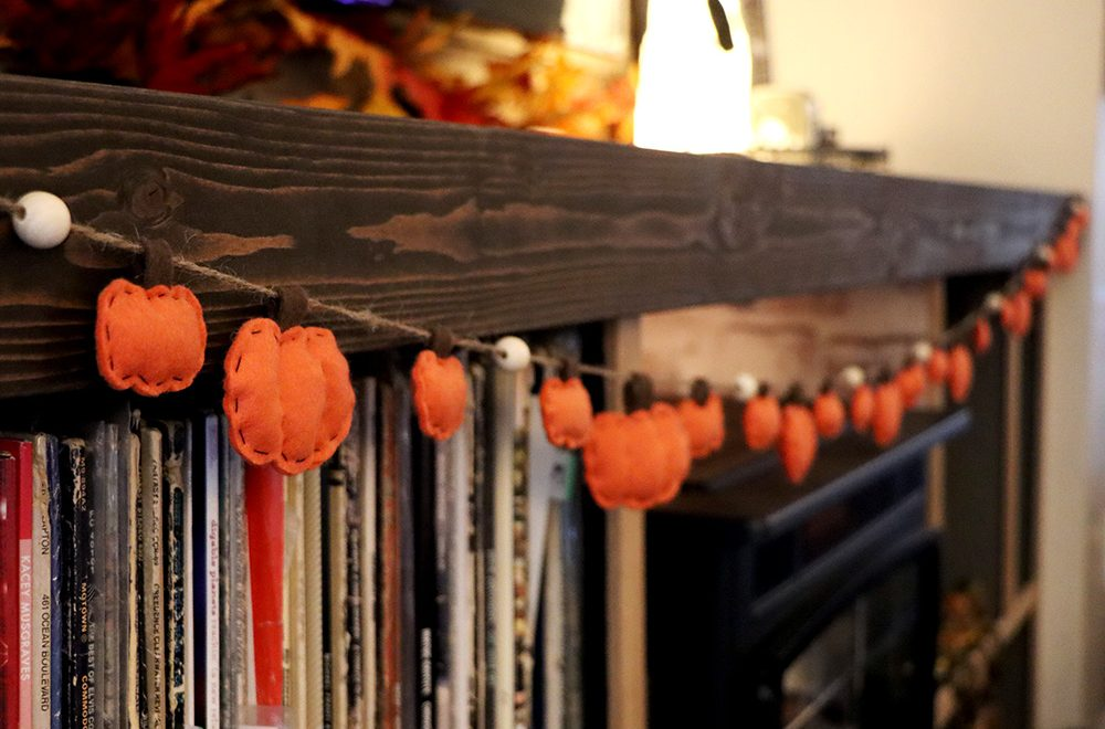A garland of pumpkins hangs from the TV cabinet